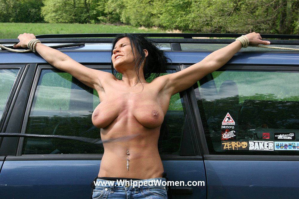 Women tied on the hood of a car
